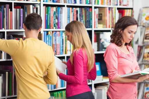 Group of people looking for books in a library.