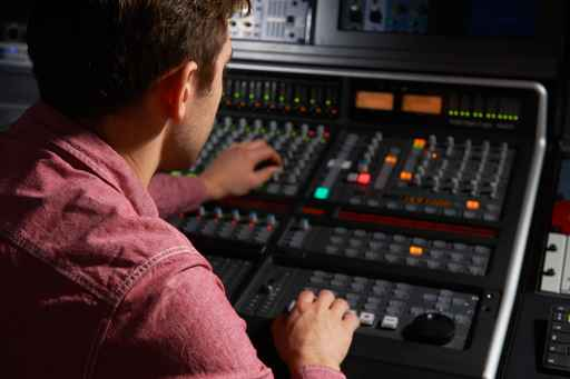 Engineer Working At Mixing Desk In Recording Studio